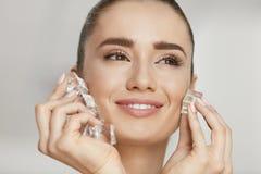 浴秀丽构成油用肥皂擦洗处理 有冰块的妇女 免版税库存照片
