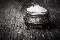 海†‹â€在一个大古色古香的盐瓶的‹盐在老木tabl 免版税图库摄影