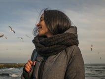 海、天空和鸥的背景的画象年轻可爱的女孩 免版税库存照片