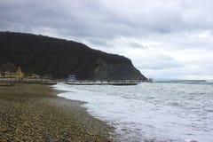 海、山、阴暗天空和含沙海岸 库存图片