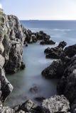 海、岩石和小船 免版税库存照片