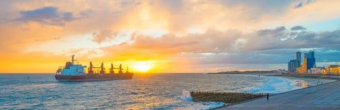 海上的小船航行沿在日落的海岸 库存照片
