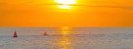 海上的小船航行沿在日落的海岸 免版税库存照片