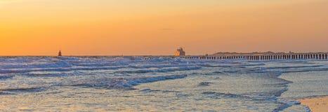 海上的小船航行沿在日落的海岸 库存图片