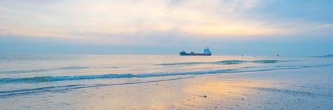 海上的小船航行沿在日落的海岸 免版税库存图片