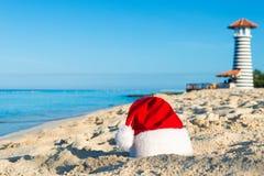 海上的新年快乐假日 在沙滩-圣诞节假日概念的圣诞老人帽子 库存图片