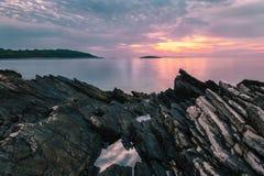 海上的日落有在前景的岩石的 库存照片