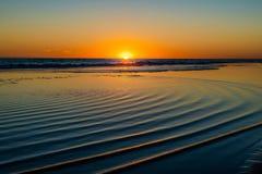海上的日落有在水的圆波浪的 免版税库存照片