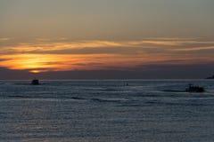 海上的船在日落期间 库存图片