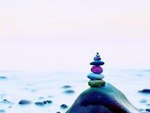 海上的被堆积的被环绕的石头 在黑暗的湿岩石,光滑的水的优美的小卵石 库存图片