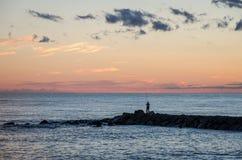 海上航行在阳光下反对晚上天空的一只大货船和在岸渔夫捉住鱼和st的日落 免版税图库摄影