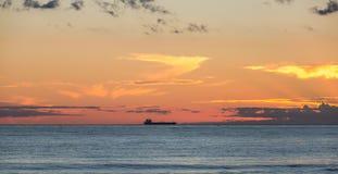 海上航行在阳光下反对晚上天空的一只大货船和在岸渔夫捉住鱼和st的日落 免版税库存照片