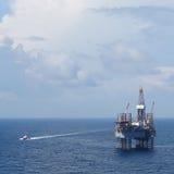 海上钻井平台(杰克凿岩机)和乘员组小船 图库摄影
