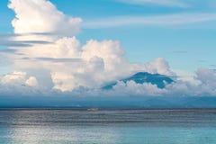 海与云彩的视图山在日落 免版税库存图片