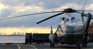 海军陆战队员一在华尔街直升机场日落的VH-3D与自由女神像在背景中 免版税库存图片