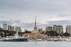 海军驻地和被停泊的小船在城市摩天大楼的背景在一个多云春天晚上 库存照片