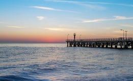 海和一个码头在日落 免版税库存图片