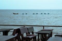 海和一家空的餐馆的看法 表和椅子没有访客 库存图片