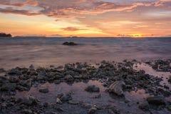 海和剧烈的暮色天空在多岩石的海滩 库存照片