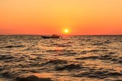 海和小船在日落 免版税库存图片