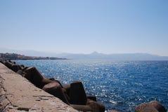海和波浪的美丽的景色在明亮的烧焦的太阳的光芒下 免版税库存图片