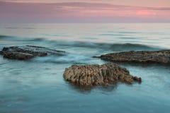 海和石头在日落以后 库存图片