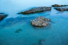 海和石头在日落以后 免版税库存照片