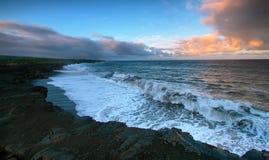 海和黑熔岩岩石的看法在日落 免版税图库摄影