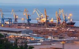 海商业口岸在晚上在马里乌波尔,乌克兰 行业视图 货物有工作的货物船抬头在海港的桥梁在t 免版税库存照片