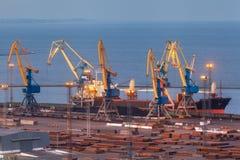 海商业口岸在晚上在马里乌波尔,乌克兰 行业视图 货物有工作的货物船抬头在海港的桥梁 免版税库存图片