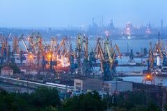 海商业口岸在晚上在马里乌波尔,乌克兰 行业视图 货物有工作的货物船抬头在海港的桥梁 免版税库存照片