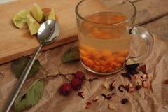 海在一个透明杯子和玫瑰果石灰的鼠李茶 有用的冬天饮料 免版税库存照片