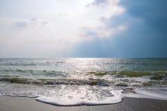 海在与风雨如磐的天空的一个沙滩挥动 库存照片