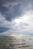 海在与风雨如磐的天空的一个沙滩挥动 免版税库存图片