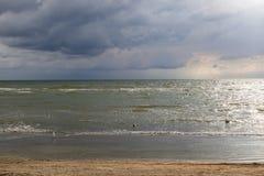 海在与风雨如磐的天空的一个沙滩挥动 库存图片