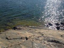 海在太阳反射的集会岩石 库存图片