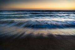 海在日落,海浪洗涤的行动挥动 库存图片