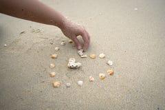 海在沙子背景的壳心脏 免版税库存照片