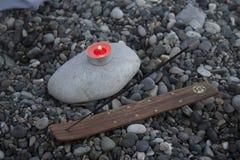 海在海滩的小卵石塔在日落,与蜡烛关闭  免版税库存图片