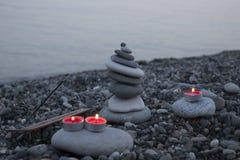 海在海滩的小卵石塔在日落,与蜡烛关闭  图库摄影