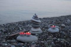 海在海滩的小卵石塔在日落,与蜡烛关闭  库存图片