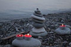 海在海滩的小卵石塔在日落,与蜡烛关闭  免版税图库摄影