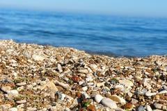 海在海的背景的小卵石沙子 免版税库存图片