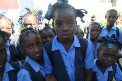 年轻海地的学校女孩好奇地为照相机摆在乡村 库存图片