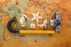 海壳、一台老照相机和废气管管在葡萄酒地图说谎 库存照片