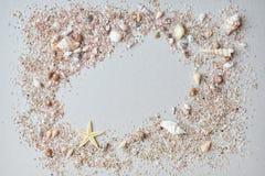 海壳和桃红色沙子与一个海星在纸背景与空的空间文本的 库存图片