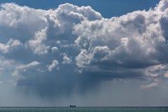 海天线在漂浮由海的船的一朵云彩 库存照片