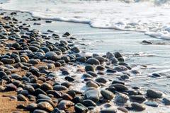 海小卵石由波浪洗涤了在日出 库存照片