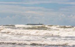 海岛和灯柱场面与强的波浪在大风天 -葡萄酒 免版税库存图片