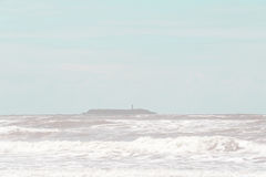 海岛和灯柱场面与强的波浪在大风天 -葡萄酒 库存照片